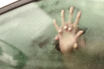 Couple holding hands having sex inside a car